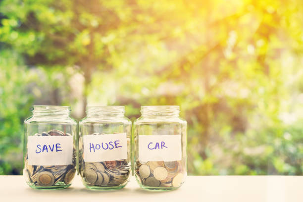 saving money for house and car concept : coins in three jars with label. ideas of saving for a down payment on a car or home that allow buyers to use down payment to reduce overall cost of borrowing. - home finances stock pictures, royalty-free photos & images
