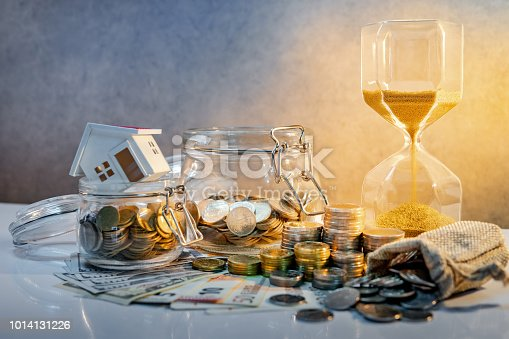 istock Saving money for retirement concept. Real estate or property investment. Home mortgage loan rate. Coin stack, money bag and currency glass jars on banknotes with hourglasses, house model on the table. 1014131226