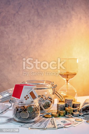 istock Saving money for retirement concept. Real estate or property investment. Home mortgage loan rate. Coin stack, money bag and currency glass jars on banknotes with hourglasses, house model on the table. 1014131288