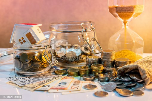 istock Saving money for retirement concept. Real estate or property investment. Home mortgage loan rate. Coin stack, money bag and currency glass jars on banknotes with hourglasses, house model on the table. 1019219664