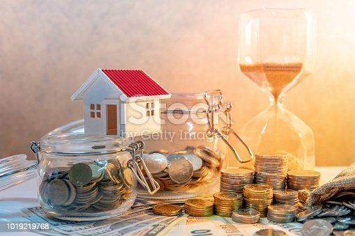 istock Saving money for retirement concept. Real estate or property investment. Home mortgage loan rate. Coin stack, money bag and currency glass jars on banknotes with hourglasses, house model on the table. 1019219768