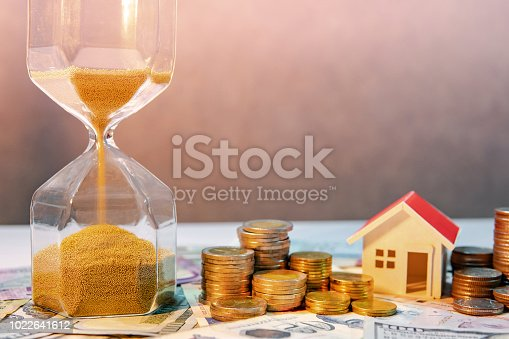 istock Saving money for retirement concept. Real estate or property investment. Home mortgage loan rate. Gold coin stack, house model and hourglasses on international banknotes. 1022641612