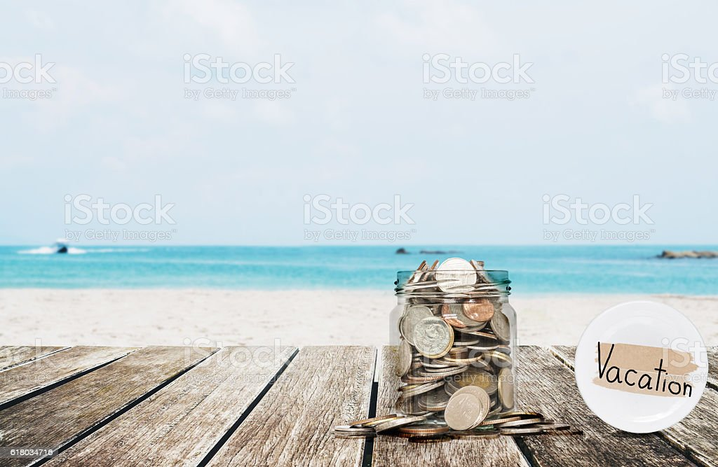 Saving money for vacation concept, glass coins container stock photo