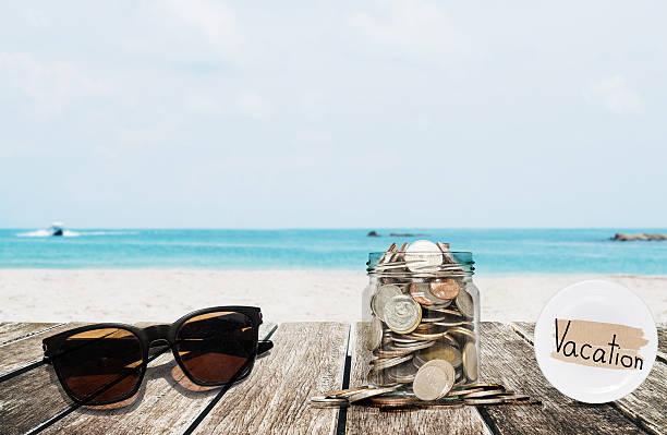 saving money for vacation concept, glass coins container with sunglasses - vakantie geld stockfoto's en -beelden