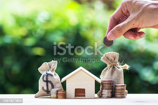 1048402108istockphoto Saving money, home loan, mortgage, a property investment for future concept : A man hand putting money coin over small residence house and money bag. 1057827804
