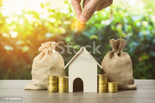 istock Saving money, home loan, mortgage, a property investment for future concept. A man hand putting money coin over small residence house and money bag with nature background. A sustainable investment. 1161808550