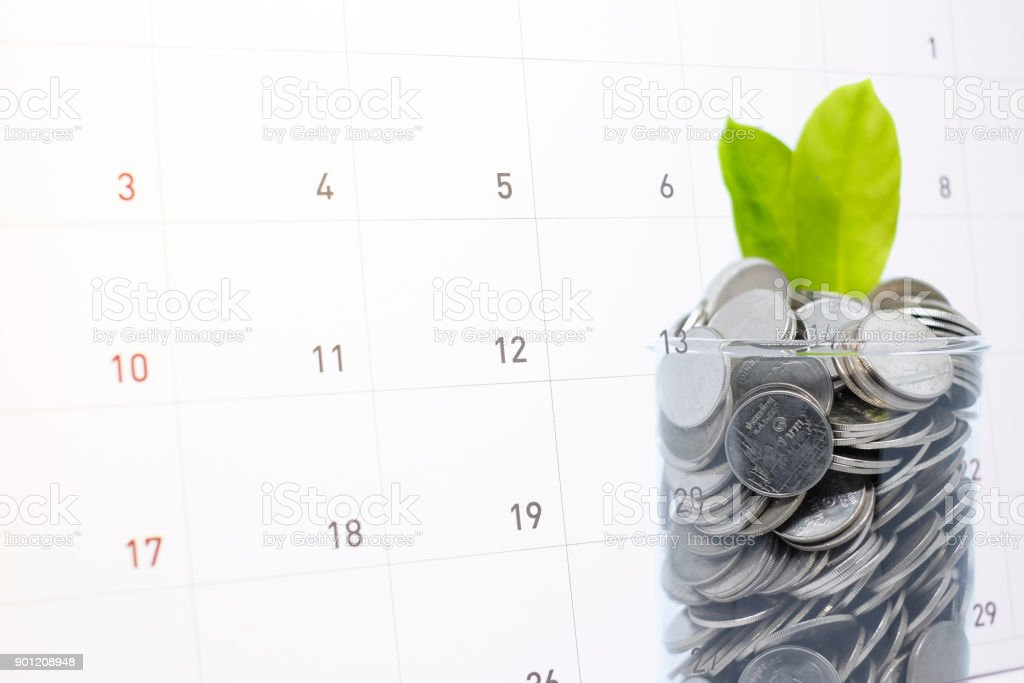Saving (frugal) money in glass for your investment future is similar to growing green leaves on tree and write a message on calender for background or texture - economical & activity 2018 concept. stock photo