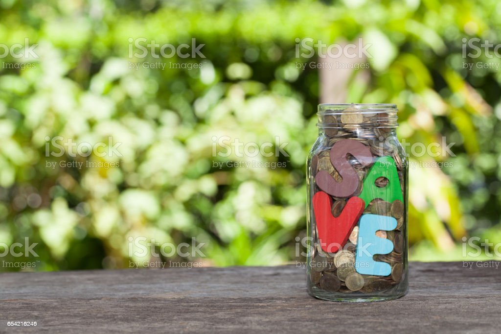 saving money into bottle for cash in future investment stock photo
