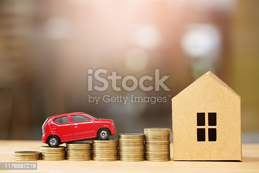 istock Saving money, Little toy car, money coins stacked on each other in different positions, house in paper model on the wooden table. Credit financial growing Loan to buy real asset concept. 1176597219
