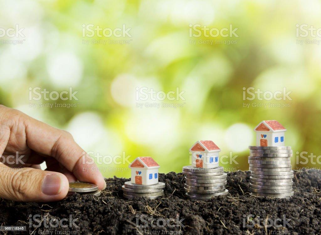 Spara pengar för att bygga ett hus-koncept, house och mynt i mark - Royaltyfri Amerikanska sedlar Bildbanksbilder