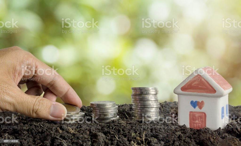saving money to build a house concept, house and coins in soil - Стоковые фото Банк роялти-фри