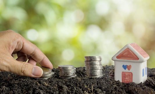 Saving Money To Build A House Concept House And Coins In Soil — стоковые фотографии и другие картинки Банк