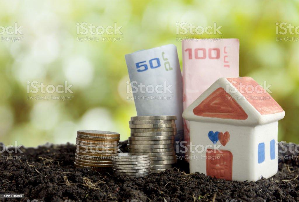 Spara pengar för att bygga ett hus koncept, hus och pengar i jord - Royaltyfri Amerikanska sedlar Bildbanksbilder