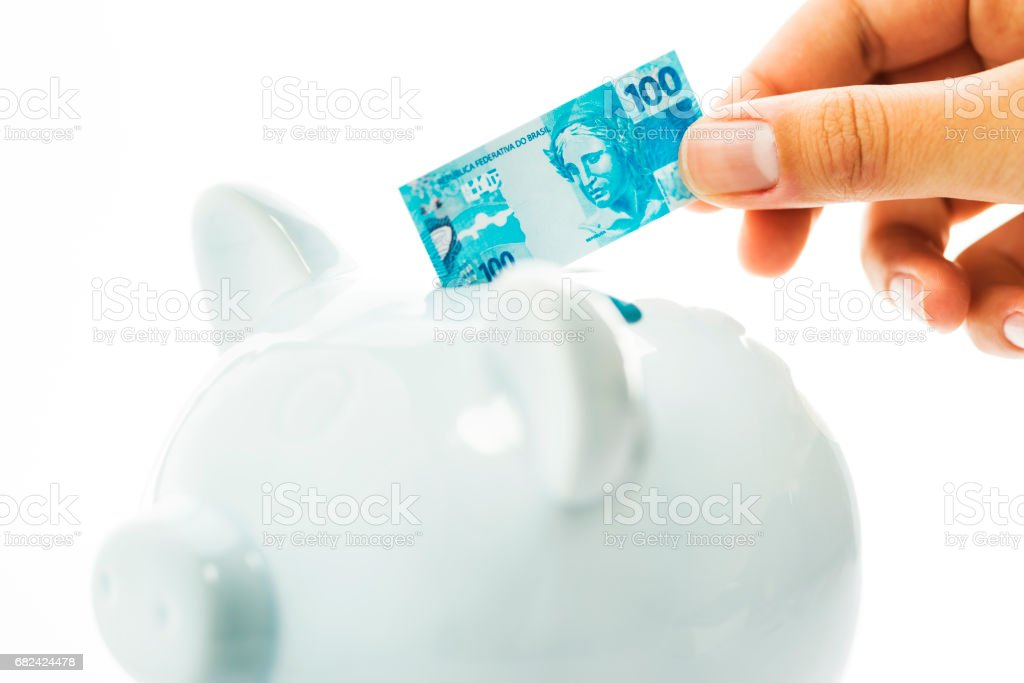 Saving money with a piggy bank, Brazilian real royalty-free stock photo