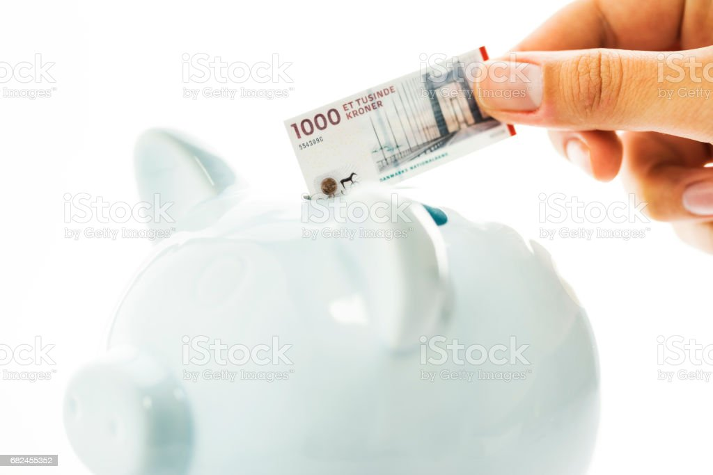 Saving money with a piggy bank, Danish krone royalty-free stock photo