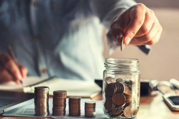 Sparen Sie Geld mit Hand setzen Münzen in Krug Glas Konzept finanzielle – Foto