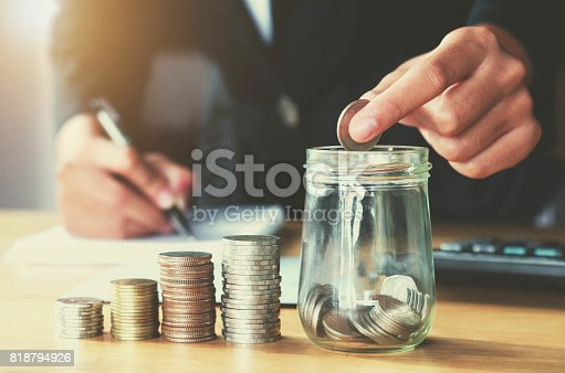 istock Saving money woman hand putting coin in jug glass concept business finance 818794926