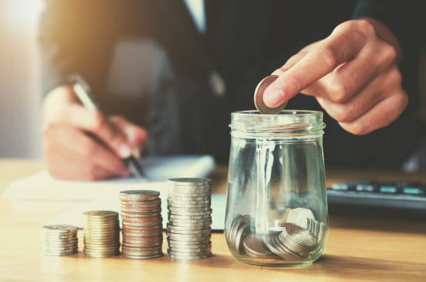saving money woman hand putting coin in jug glass concept business finance - wages stock photos and pictures