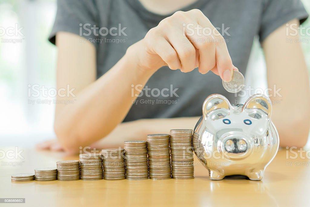 Sparen-junge Frau, die eine Münze in eine Geld-box-Nahaufnahme – Foto