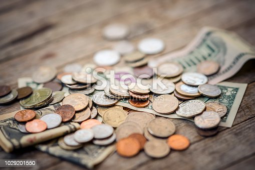 American banknotes and coins on wooden surface