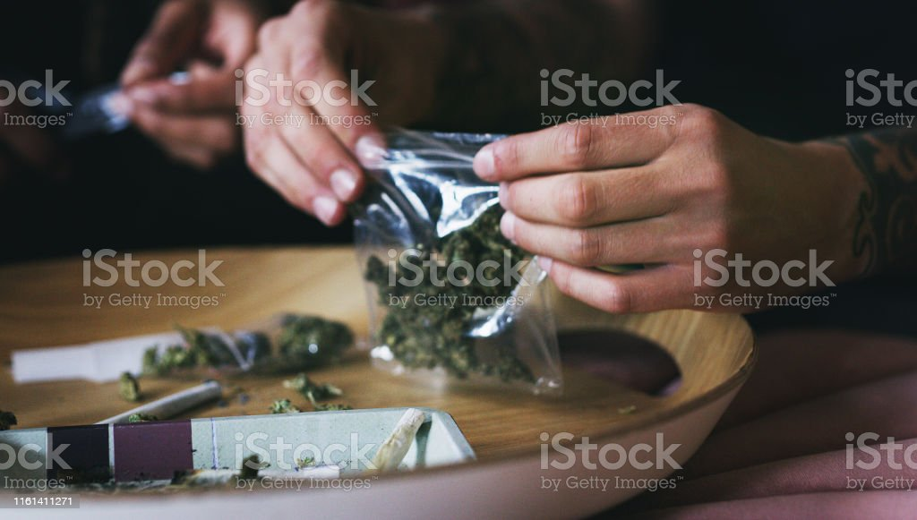 Saving some for later Cropped shot of a man rolling a marijuana joint at home Abuse Stock Photo