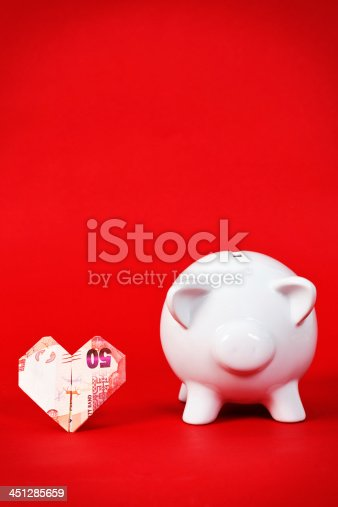 istock Saving up for love! Origami dollar-bill heart with piggybank 451285659