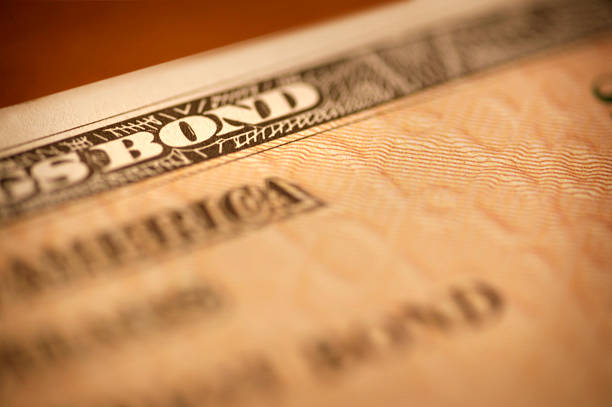 savings bond close up - stock certificate stock photos and pictures