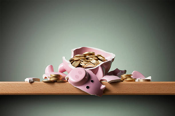 Savings. Broken piggy bank with coins. stock photo