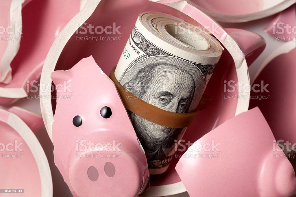 Savings. Broken piggy bank with dollars banknotes royalty-free stock photo