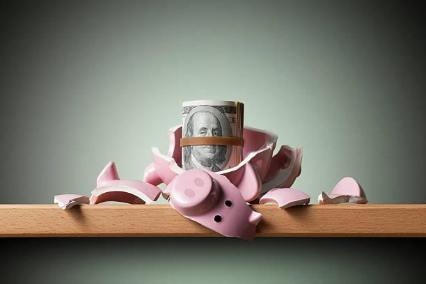 Savings. Broken piggy bank with dollars banknotes stock photo
