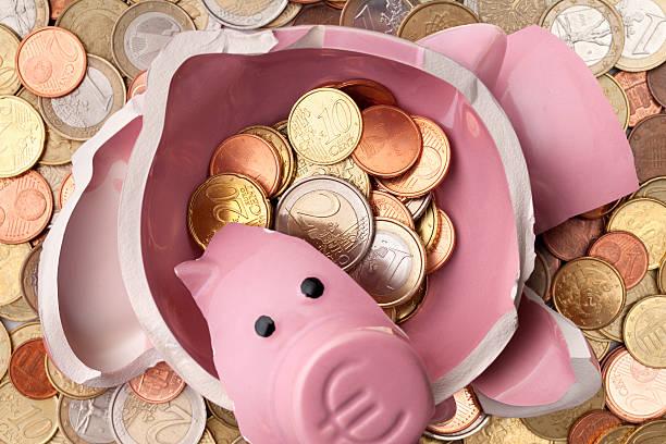 Savings. Broken piggy bank with euro coins stock photo
