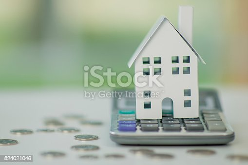 A white metal toy house sits on a calculator and is surrounded by coins. Illustrating the concepts of cost and expenses of real estate and buying a new home.