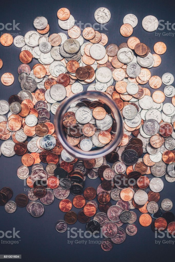 Savings jar filled with cash surrounded by coins stock photo