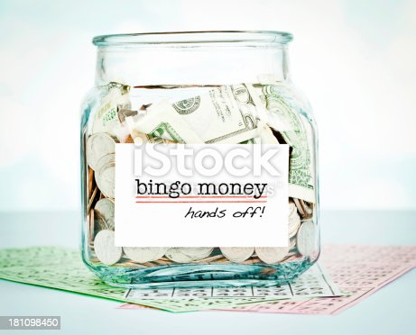 Glass jar containing money for bingo and a label issuing a warning!