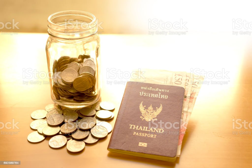 Savings jar with currency for travel stock photo