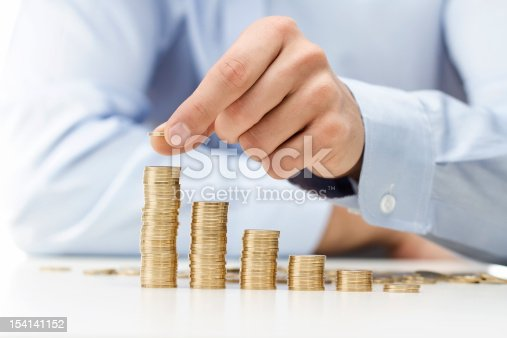 Close up of male hand stacking gold coins into increasing columns