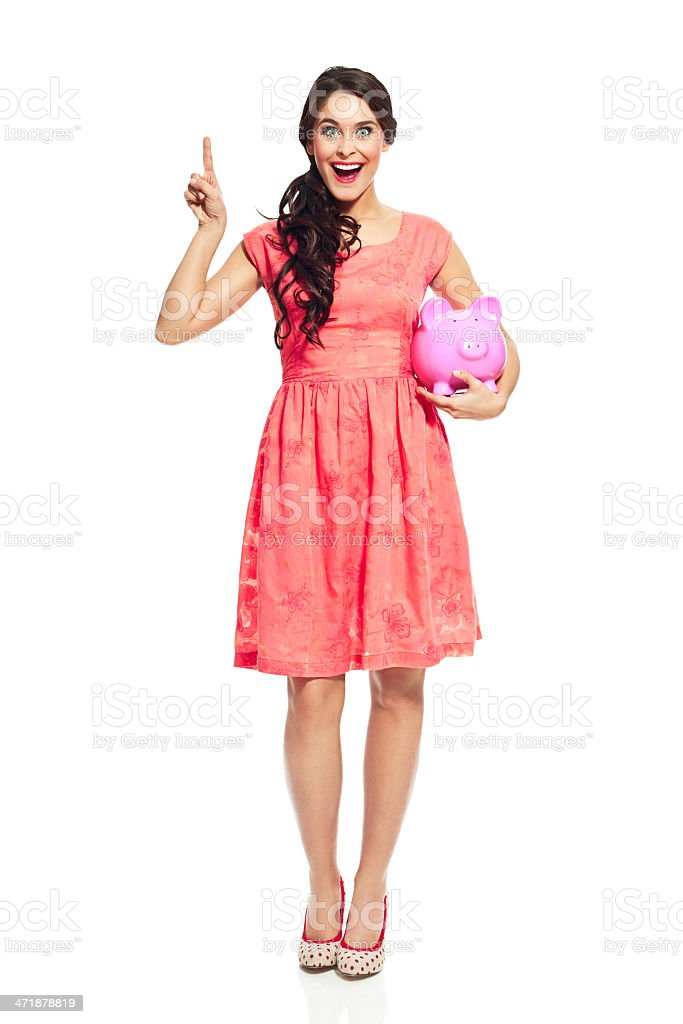 Savings Full lenght portrait of beautiful young woman holding pink piggybank in hand and smiling at camera. Studio shot, isolated on white. 20-24 Years Stock Photo