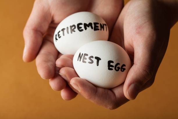 Savings. Hands Holding Two Eggs Marked Retirement And Nest Egg nest egg stock pictures, royalty-free photos & images