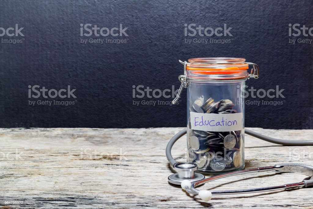 Savings plans for education and medical stethoscope on wooden table, financial concept royalty-free stock photo
