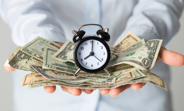 Savings Time Woman holding paper currency and alarm clock. time is money stock pictures, royalty-free photos & images