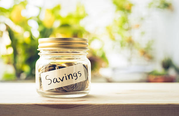 Savings word with money coin in glass jar.financial concept stock photo