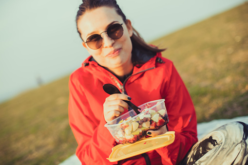 A beautiful woman is holding a delicious fruit salad and looking at the camera.