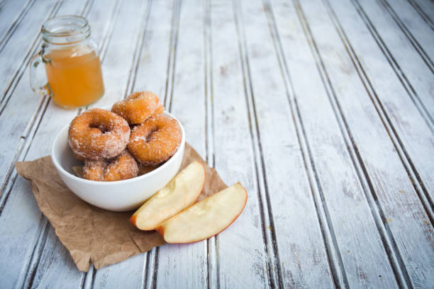 Savory Apple Cider Donuts Sweet and savory apple cider donuts on a table. hot apple cider stock pictures, royalty-free photos & images