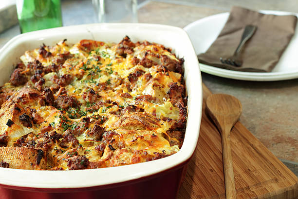 savory breakfast casserole next to wooden spoon - casserole stock photos and pictures