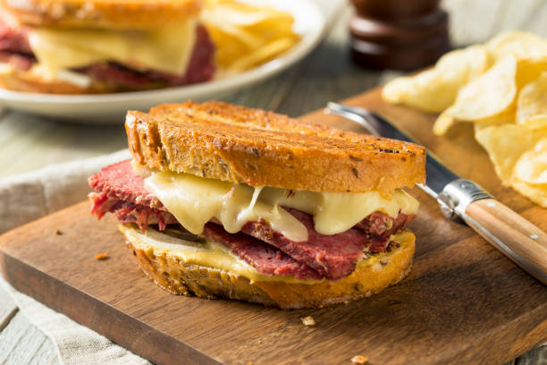 savory homemade corned beef reuben sandwich - pastrami stock pictures, royalty-free photos & images