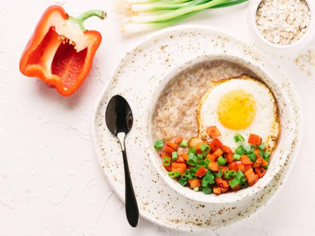 farinha de aveia salgada, servida com legumes e ovo frito - comida salgada - fotografias e filmes do acervo