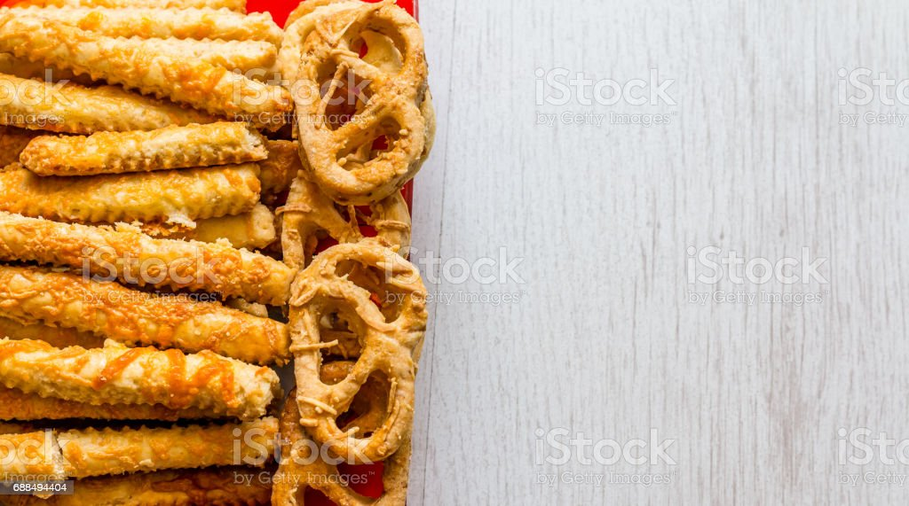 Savory pretzels in the traditional looped knot shape and sticks with cheese in a random heap viewed from overhead stock photo