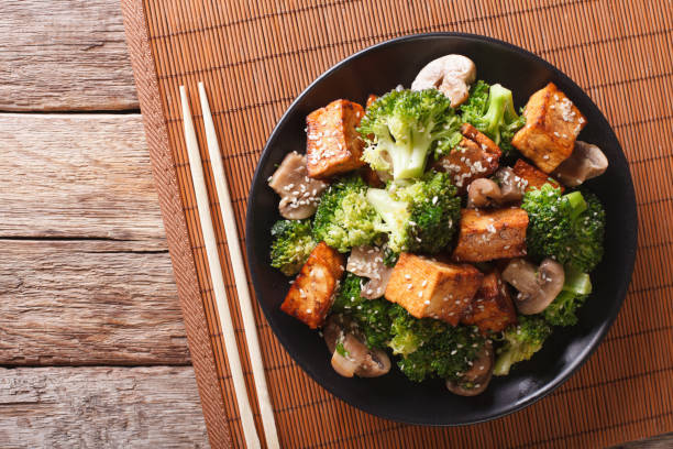 Savory sauteed mixed chinese vegetables with crispy fried tofu. Horizontal top view Savory sauteed mixed chinese vegetables with crispy fried tofu on a plate. Horizontal view from above asian food stock pictures, royalty-free photos & images