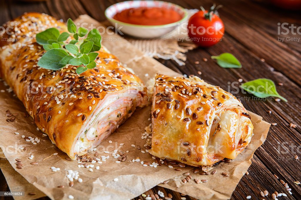 Savory strudel with ham, cheese, tomato sauce and herbs stock photo