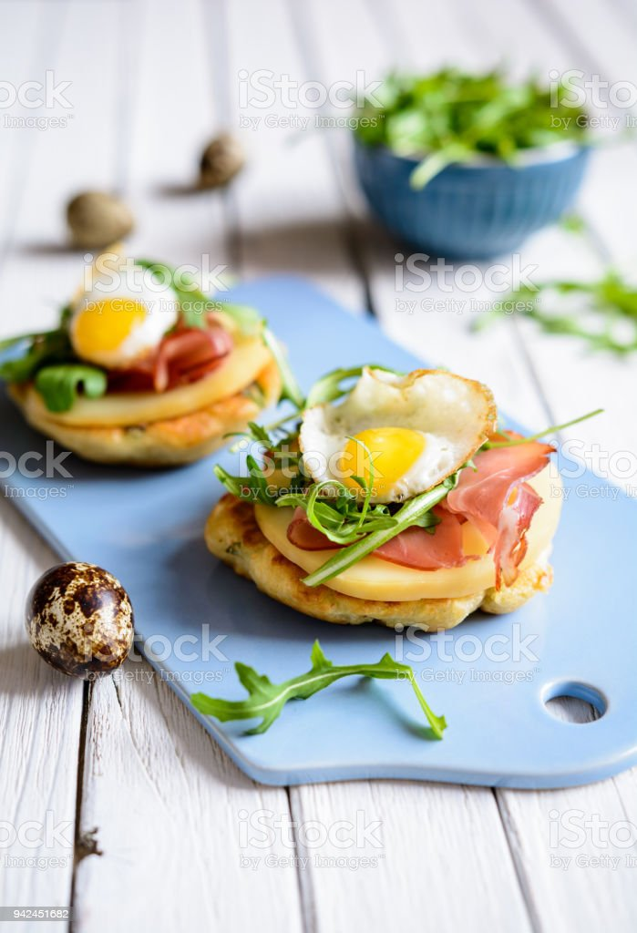 Savoury yoghurt and scallion pancakes with Black Forrest ham, smoked cheese, quail egg and arugula stock photo